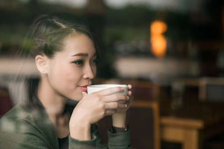 Close-up portrait of young lady enjoying a cup of hot tea Stock Photo