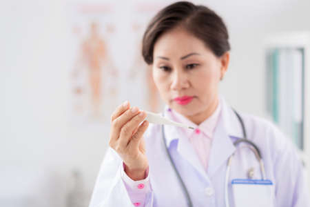 Vietnamese female doctor looking at the thermometer