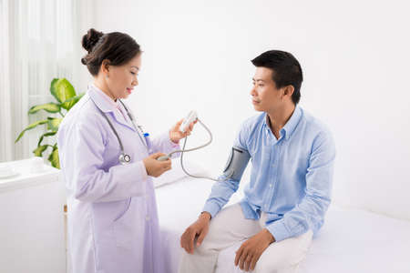 Asian doctor using electronic tonometer to check blood pressure of the patient Reklamní fotografie