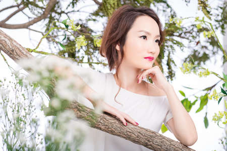 Portrait of beautiful Chinese woman in summer garden Stock Photo