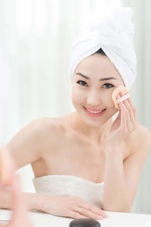 Young beautiful woman applying make-up after shower Stock fotó