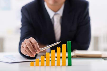 Businessman using pen to indicate ascending bar graph Stock Photo