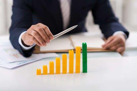 visualizing: Visualization of uptrend: businessman showing column chart made of toy bricks
