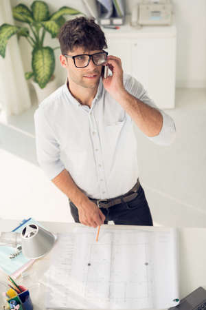 homeoffice: Portrait of young handsome architect talking on the phone