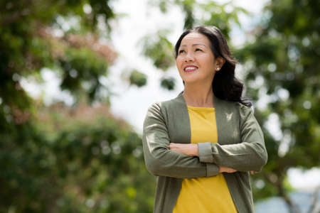 Mature Vietnamese woman enjoying sunny day in the park Stock Photo