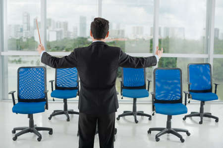 baton: Businessman conducting his invisible employees, rear view