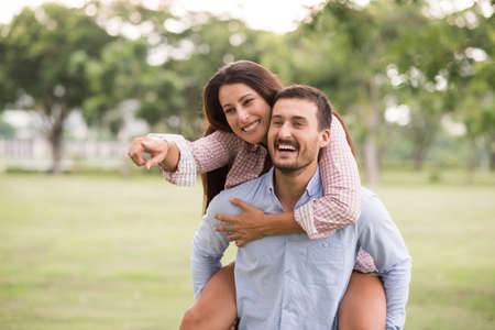 Happy handsome man piggybacking his girlfriend in the park Stock Photo