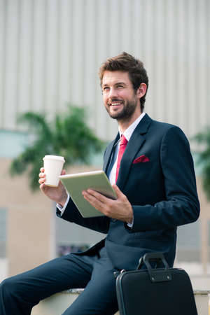 Joyful entrepreneur sitting outdoors with a tablet and take-out coffee