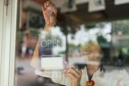 Lächelnde Frau, die offenes Zeichen auf der Glastür hängt Standard-Bild