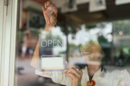Smiling woman hanging open sign on the glass door