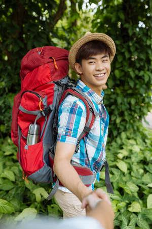 Joyful Asian hiker holding hand of his girlfriend