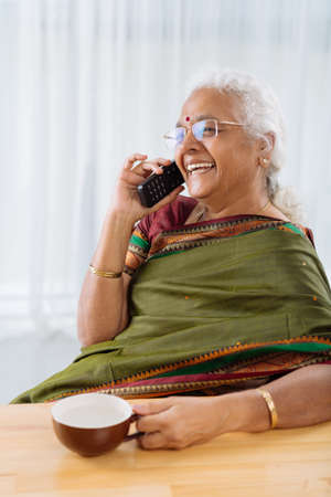 Happy mature Indian woman in sari talking on the phone