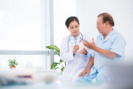 Doctor giving pills to her patient in hospital 版權商用圖片
