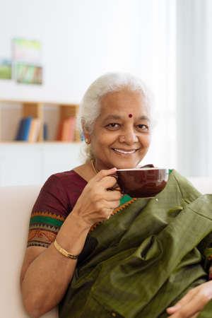 Gelukkige rijpe Indische vrouw die thee heeft