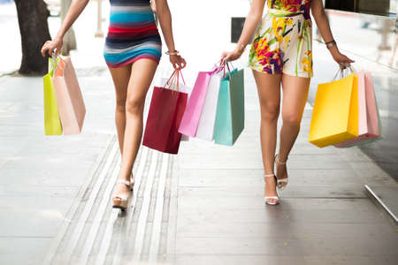 Two females walking with shopping bags in hands Stock Photo