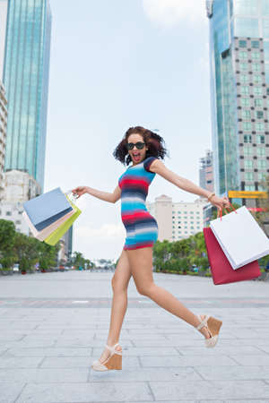 or spree: Young women jumping with delight with shopping bags