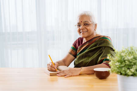 Happy Indian woman on retirement looking at camera Banco de Imagens - 74809835