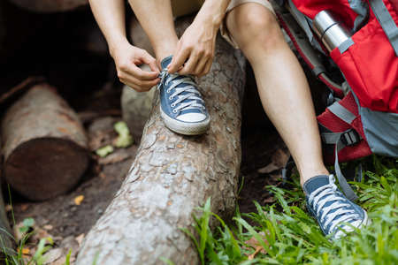 Male hiker tying shoelaces in summer forest
