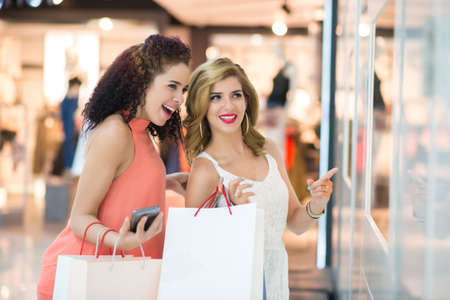 Woman pointing at shop window to her friend