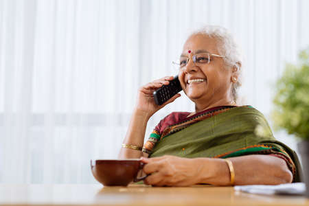 Happy mature Indian woman with telephone talking to somebody