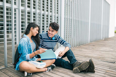 Young couple reading for lesson together and talking