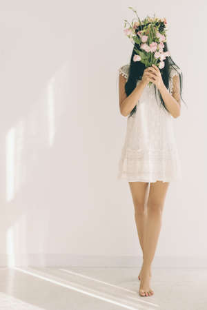 Young woman standing on tiptoes and hiding behind bouquet of flowers
