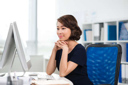 vietnamese ethnicity: Pretty office worker looking at computer screen Stock Photo