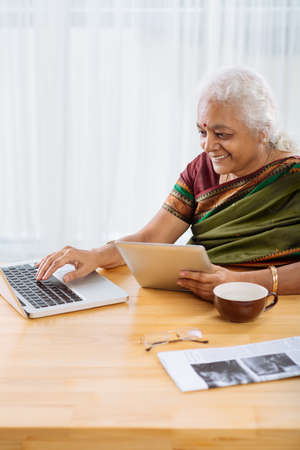 Mature Indian woman using laptop and touchpad simultaneously