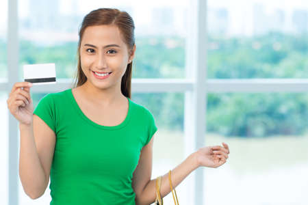 Portrait of smiling Asian woman holding paper-bags and credit card Stock Photo