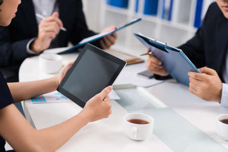 Women sitting with touchpad at important meeting