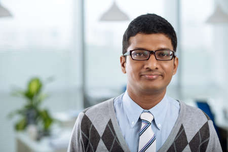 Portrait of young Indian businessman smiling and looking at the camera
