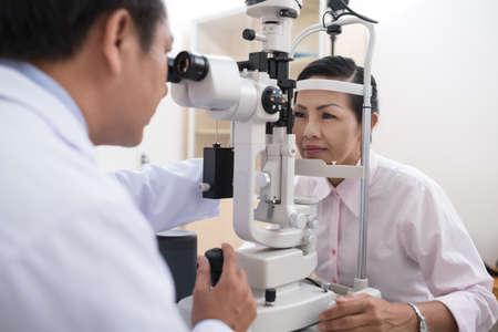 Hogere Aziatische vrouw die zichtonderzoek heeft Stockfoto
