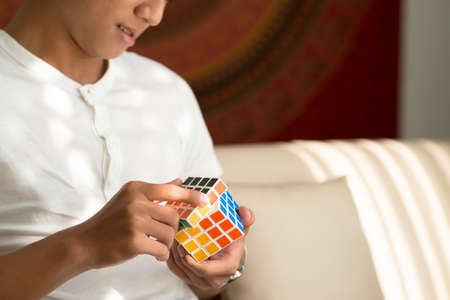 Ho Chi Minh City, Vietnam – May 14, 2015: Man solving Master Cube, variation of Rubik's cube, invented by Peter Sebesteny