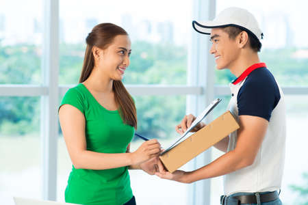 Delivery man giving young woman a document to sign Stock Photo