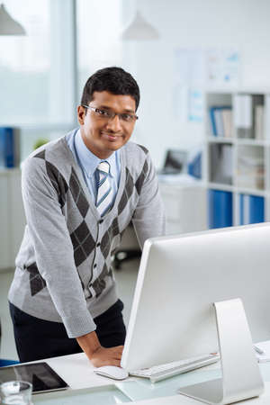 Smiling Indian manager standing at his workplace