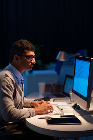 Young Indian programmer working overtime in the office