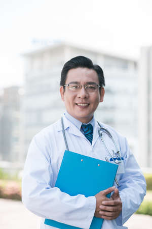 Portrait of experienced Asian practitioner with a folder Stock Photo