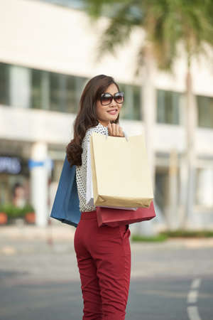 Portrait of smiling pretty woman with paper-bags