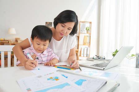 Madre asiatica e figlio disegno sul posto di lavoro Archivio Fotografico