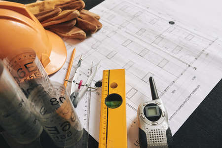 Different belongings of engineer on blueprint of building