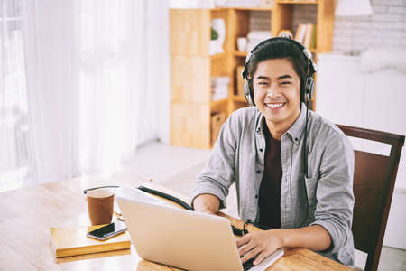 Asian student in headphones working on laptop at home Фото со стока