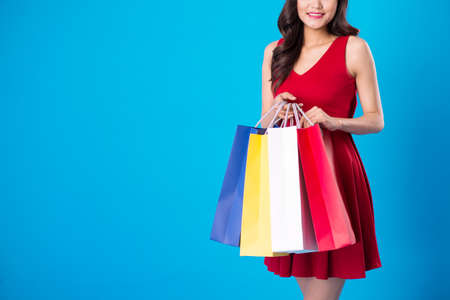 Cropped image of smiling woman holding shopping bags