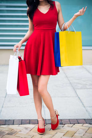 Cropped image of woman in bright red dress holding paper bags