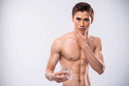 Sensual Asian man applying aftershave Stock Photo