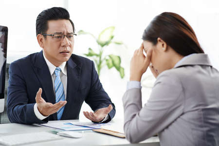 Angry businessman talking to his crying female assistant