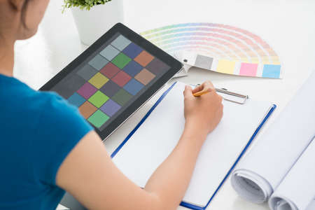 architect drawing: Female designer choosing perfect color for future interior, view over the shoulder