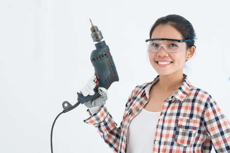 Lovely young woman with a drill: home repair concept Stock Photo