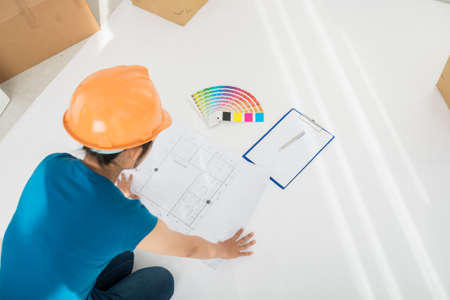 Designer looking at plan of the building before work
