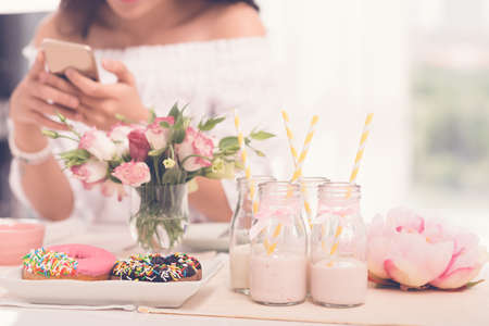 Party table with drinks and sweets and texting woman in the background Stock Photo