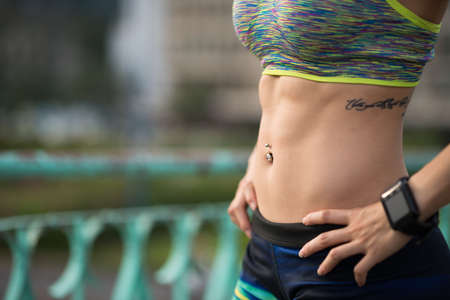 Beautiful fit female belly with navel piercing Stock Photo